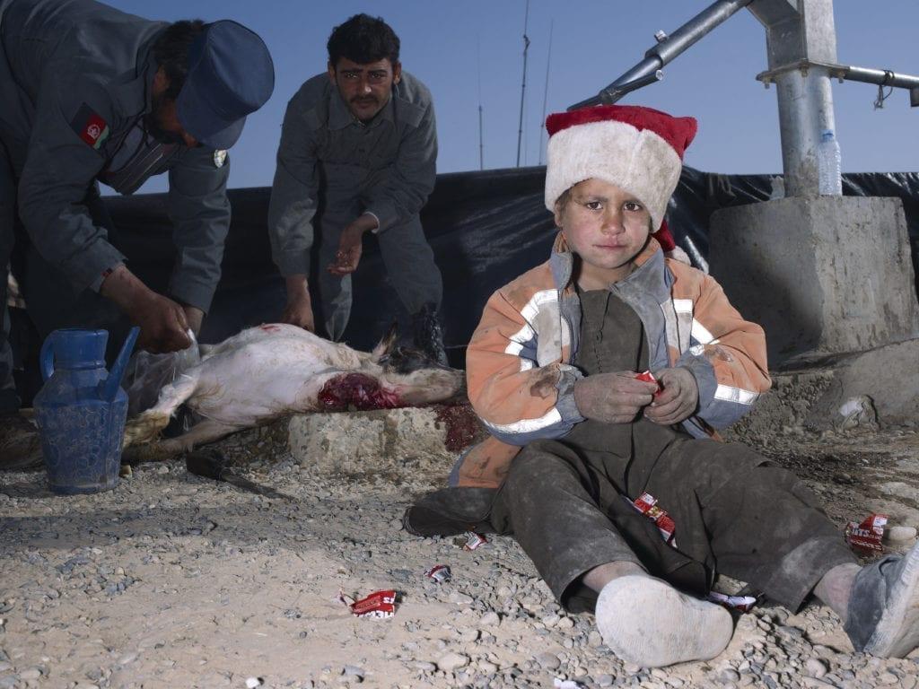 mark-neville-child-jacket-slaughtered-goat-sweets-painted-nails-xmas-day-helmand-2010-courtesy-mark-neville