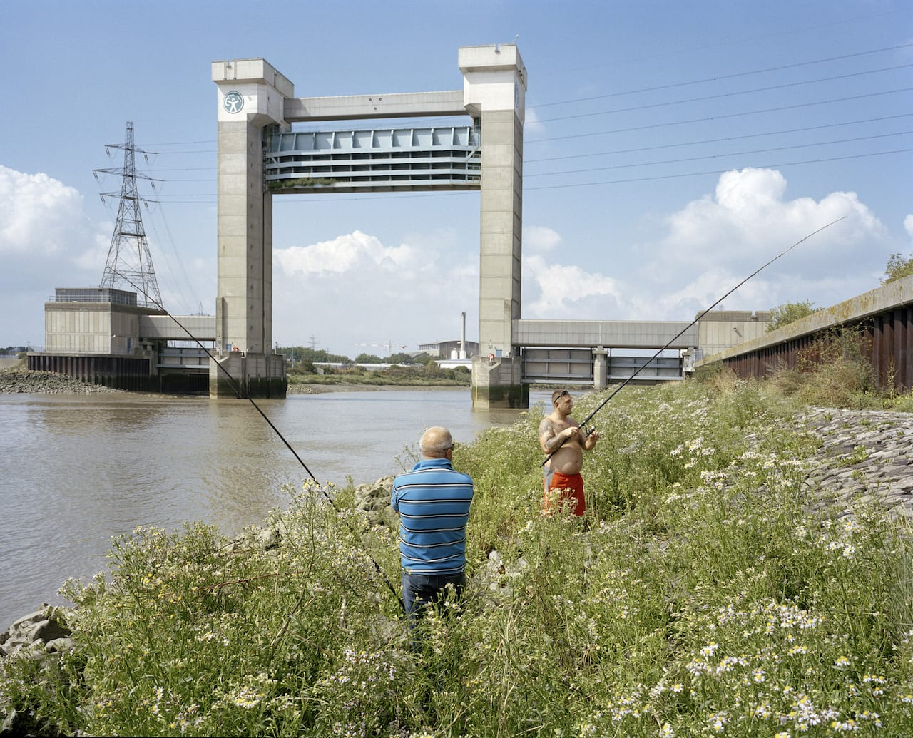 Fishermen at the mouth of Barking Creek. With raised flood barrier in the background. From the series London Ends © Philipp Ebeling
