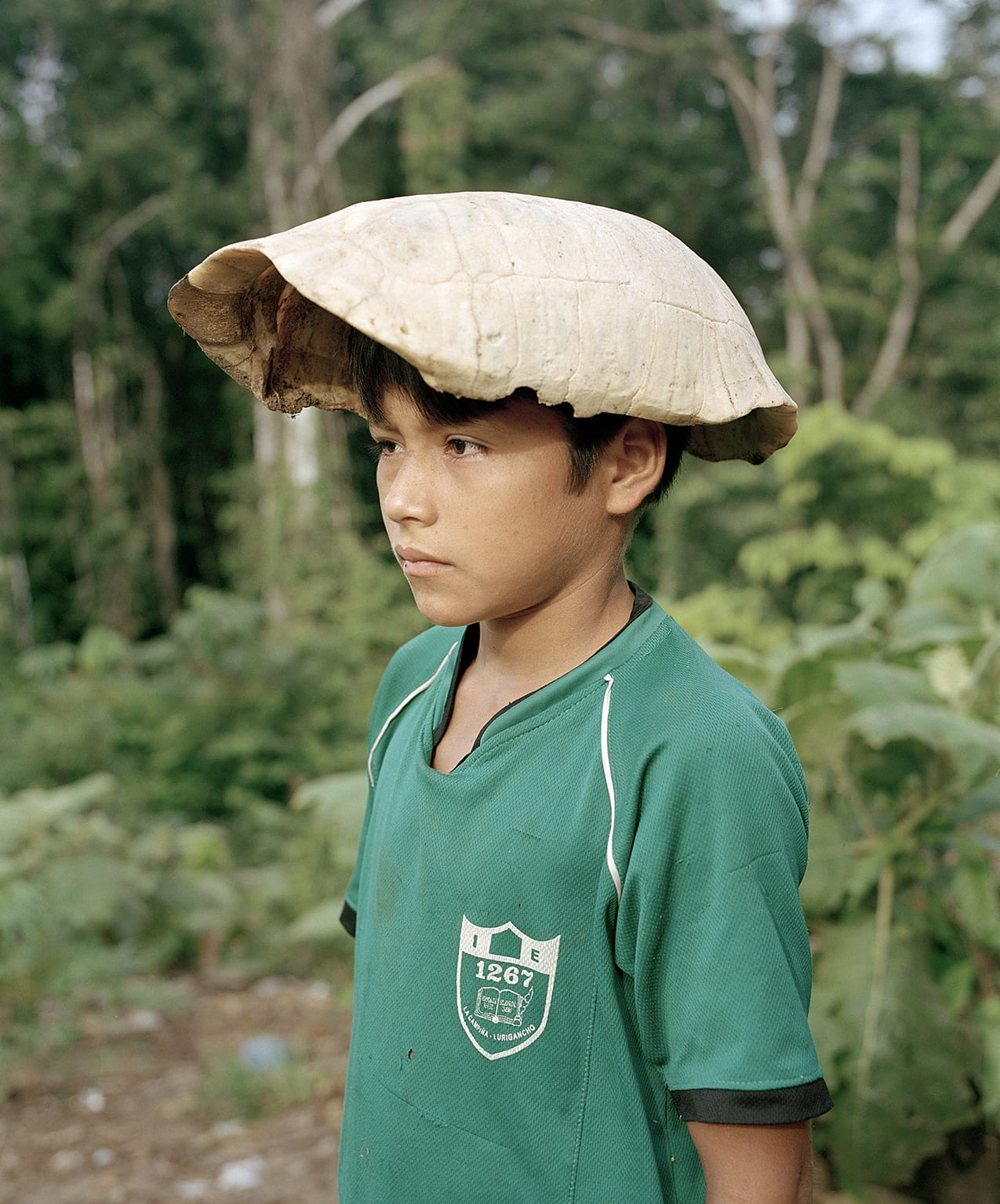 Yann Gross, The Turtle Cap, 2012, from The Jungle Book (Aperture, 2016)  After lunch, a kid plays with a turtle shell, Bolívar Community, Peru. Turtle is one of the favorite meals in the Amazon.
