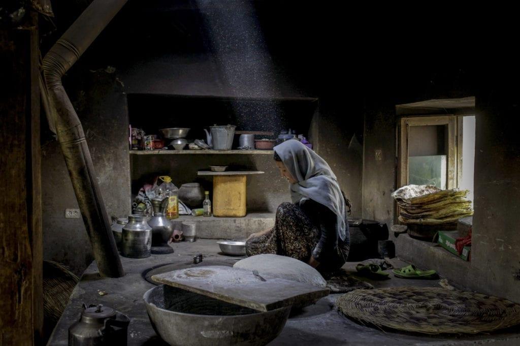 Afghanistan. 2011. An Afghan woman bakes bread in the border town of Badakhshan.