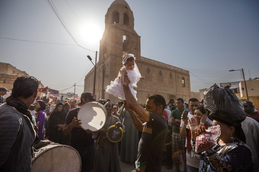 A family celerates a baptism as part of the moulid festival in Minya. Families from across Egypt make their way to Minya during the week of the festival in hopes of having their babies baptized as they believe it will bring them greater luck. After the baptismal ceremony, families parade the infants around town while bands play music to celebrate.