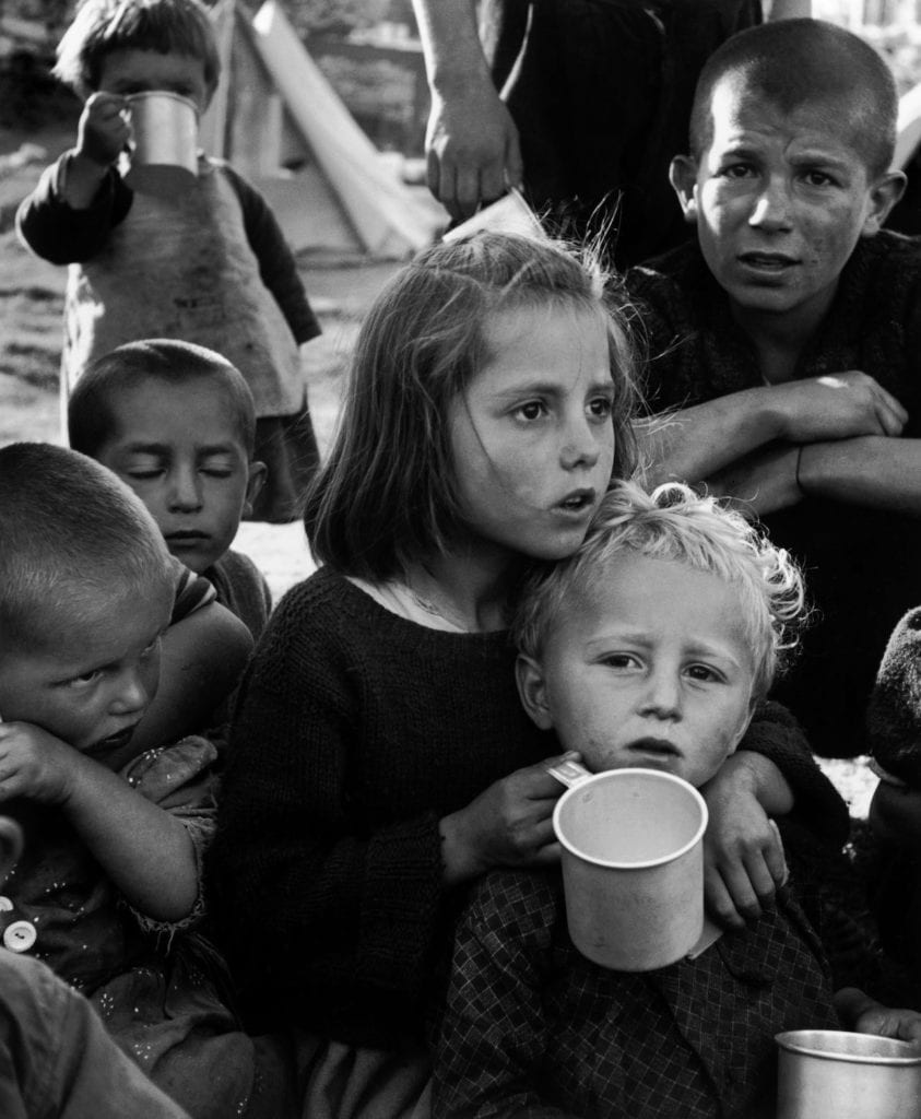 """Refugees from the civil war areas. Waiting for this unfamiliar stuff, UNICEF milk (reconstituted from powdered milk) distributed for the first time at the refugee camp. Ioannina, Greece, 1948 © David """"Chim"""" Seymour/Magnum Photos"""
