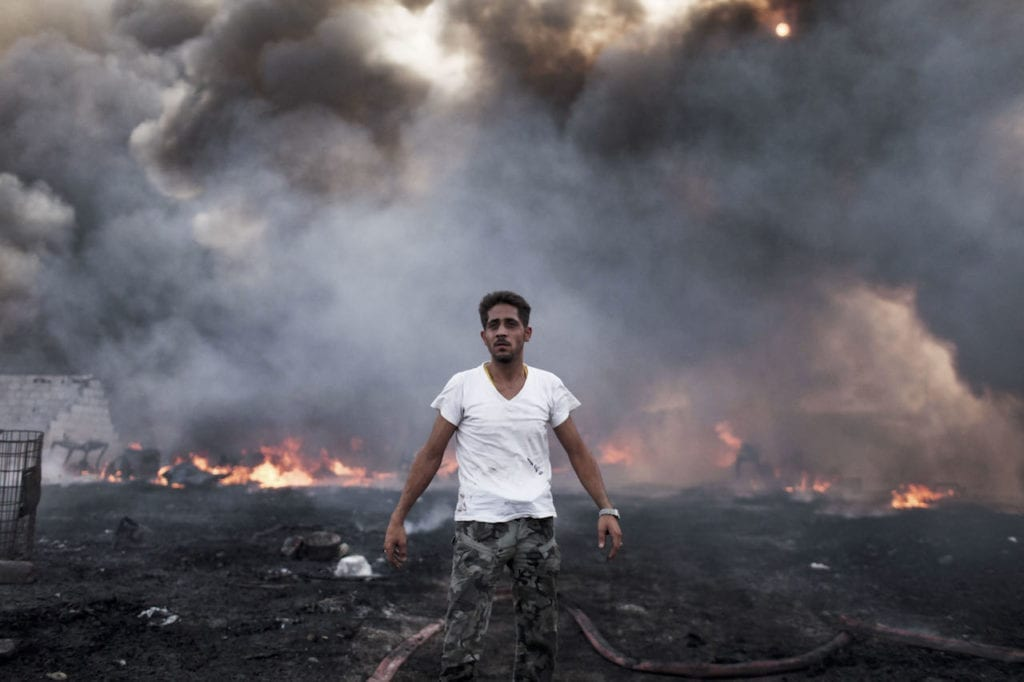 A man stands at the scene of a fire - suspected arson - that destroyed a plastic factory in the Khatba district of Tripoli. Khatba was a stronghold of Qaddafi supporters and the scene of heavy fighting between Qaddafi loyalists and rebels during the battle for Tripoli. Libya, 05 September 2011 © Moises Saman/Magnum Photos