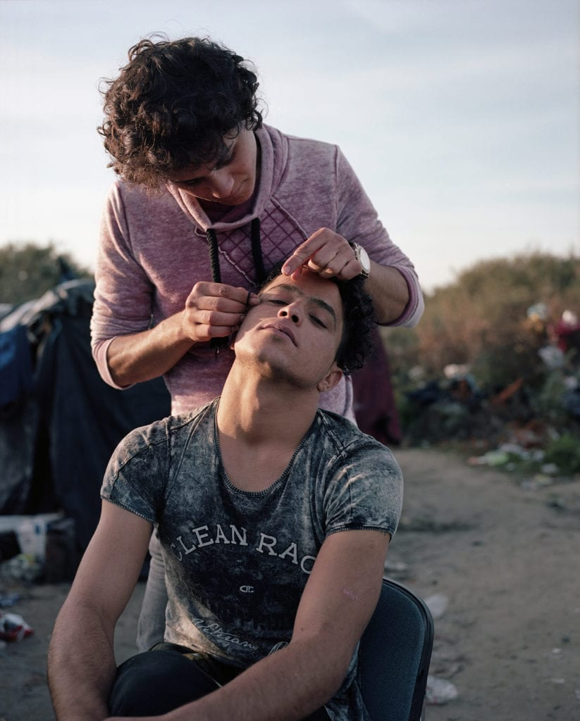 North African men threading their eyebrows. Calais, France, November 2015. From the series Foreigner: Migration into Europe 2015-2016 © Daniel Castro Garcia