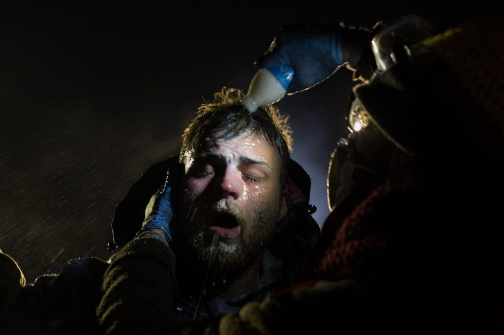 Healers - A man is treated after being pepper sprayed by police. White people have joined the camps in large numbers, often standing in front of indigenous protestors to shield them with their bodies. A man is treated with milk of magnesia after being pepper sprayed at the police blockade on highway 1806 near Cannon Ball, North Dakota on Sunday, November 20, 2016. Many people were injured when, with temperatures below freezing, police deployed water canons, pepper spray, tear gas, rubber bullets and percussion grenades. Amber Bracken
