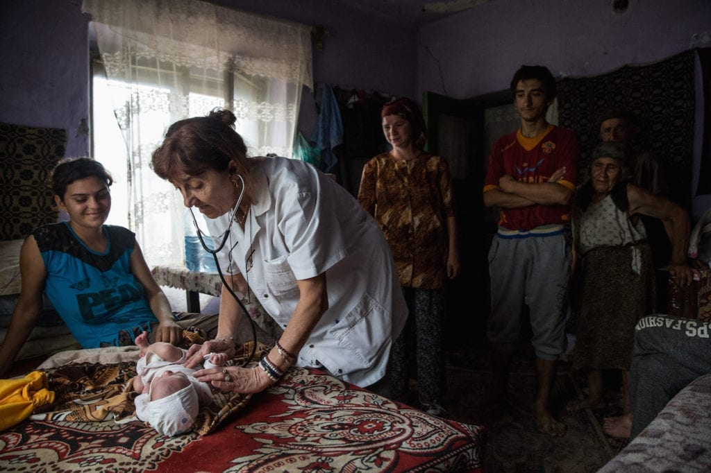 Dr. Ciupitu doing a house call to consult on an infant. The child had otitis due to improper bathing. According to Eurostat data, with an infant mortality rate of 8.4 deaths per 1000 live births in 2014, Romania ranks first among European countries (the EU rate is 3.7). Gangiova, Romania, 18 August 2016. From the series A country doctor and her calling © Ioana Moldovan, Romania, shortlist, Professional, Daily Life, 2017 Sony World Photography Awards
