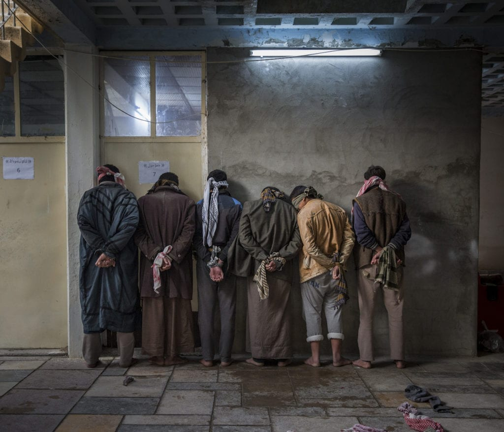 Iraqi men from the Hawija region of Iraq wait to be questioned by Kurdish security personnel at a base near Kirkuk. Having fled areas still under the control of ISIS militants, men and boys of fighting age are vetted for any links to the group before being allowed to join their families in camps for displaced people in the Kurdish controlled region of the country. From the series Caught in the Crossfire © Ivor Prickett, Ireland, shortlist, Professional Current Affairs & News, 2017 Sony World Photography Awards