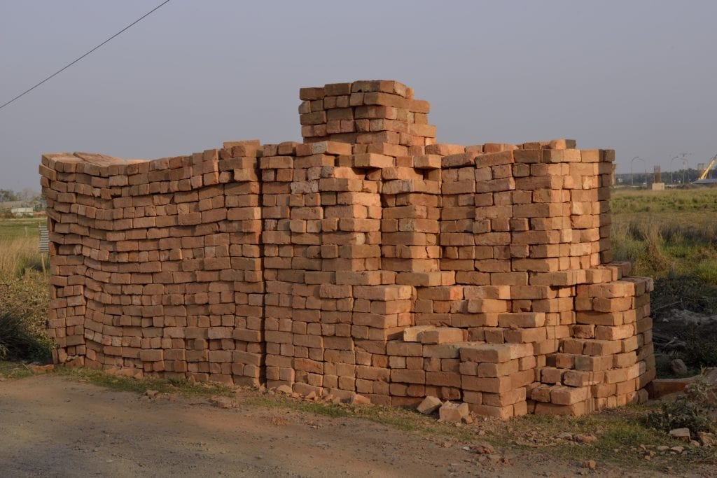 """Bricks dating back to 7500 BC have been found at Tell Aswad in the upper Tigris region of what is now modern Syria. In Exodus 1:14; 5:4-19 we are told that the Egyptians """"came to dread the Israelites and worked them ruthlessly. They made their lives bitter with harsh labor in bricks and mortar."""" Straw and sand were added to mud and kneaded by foot for days before being set in molds. Union Solidarity International has been campaigning against """"blood bricks' in India since 2012. In the words of Andrew Brody, """"its modern day slavery. Entire families of men, women, and children are working for a pittance, up to 16 hours a day in terrible conditions. There are horrific abuses of minimum wage rates and health and safety regulations, and it's often bonded labor, so they can't escape."""" Bricks, Outskirts of Kolkuta, India, March, 2014 © Joel Sternfeld. Image courtesy of Luhring Augustine and Beetles+Huxley"""