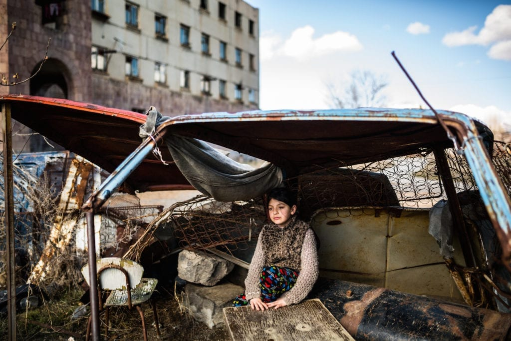 """Syuzanna, nine, sitting in a """"shelter"""" made of rusty old car parts. Ten days ago Syuzanna's father committed suicide, people say, because of debt. In 1988, a 7.0 Richter-scale earthquake struck northern Armenia. The quake killed at least 25,000 people in the region. Thousands more were maimed and hundreds of thousands left homeless. Gyumri, Armenia's second largest city bore much of the damage. Large-scale war by the early 1990s, the collapse of the Soviet Union, an energy shortage, and a blockade that left landlocked Armenia with just two open borders, contributed to exacerbating the region's already prevalent social and economic problems. A quarter of a century later, Gyumri has the country's highest poverty rate at 47.7%. The city has lost nearly half of its population since 1988, due in part to the migration of the labour force. A few thousand families are still living in makeshift shelters, waiting for help. From the series Inhabitants of the Empty © Yulia Grigoryants, Armenia, shortlist, Professional, Daily Life, 2017 Sony World Photography Awards"""