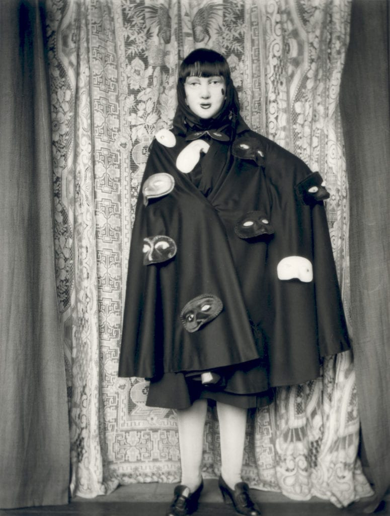 Self-portrait (full length masked figure in cloak with masks) by Claude Cahun, 1928 © Jersey Heritage