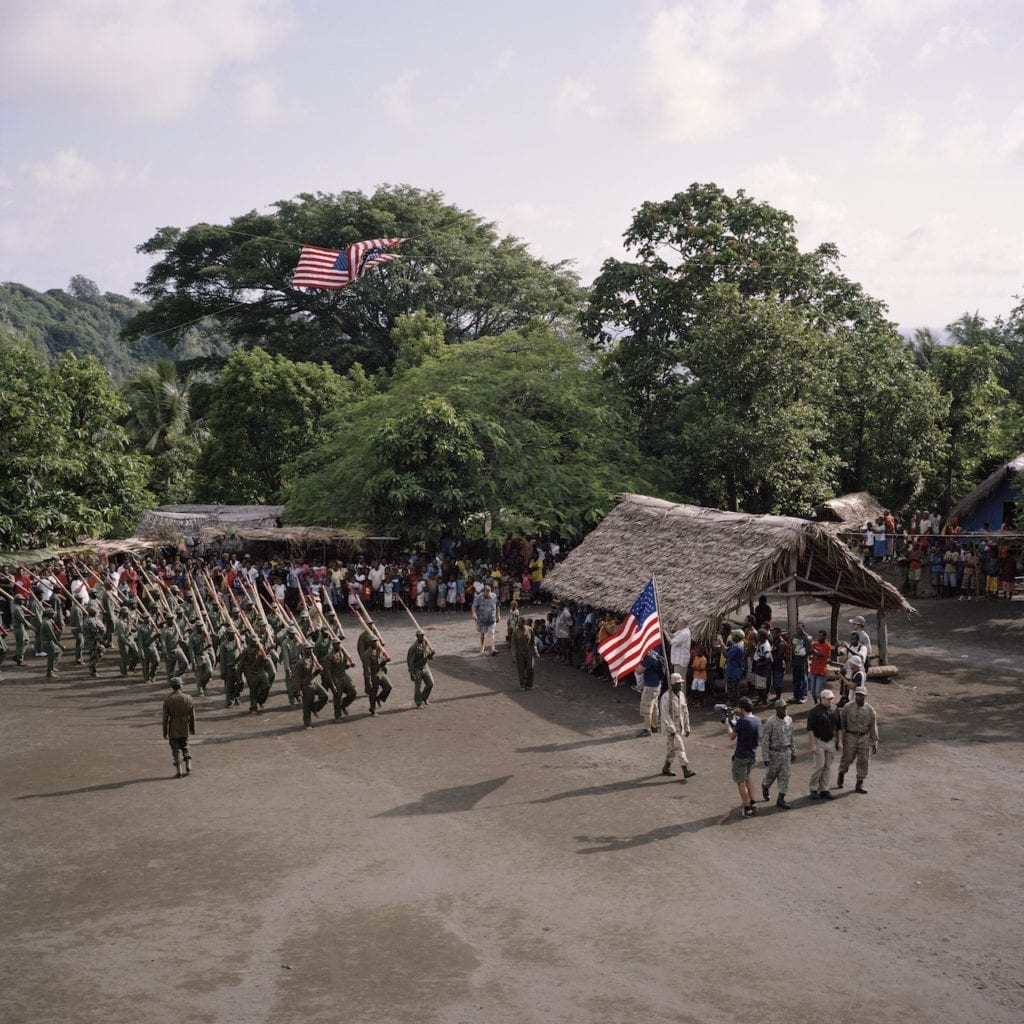 The John Frum Day celebrations on Tanna in February 2014. The villagers can be seen here marching with bamboo rifles as part of their annual ceremony, with Cevin, the American filmaker at the front of the line. From the series Cargo © Jon Tonks