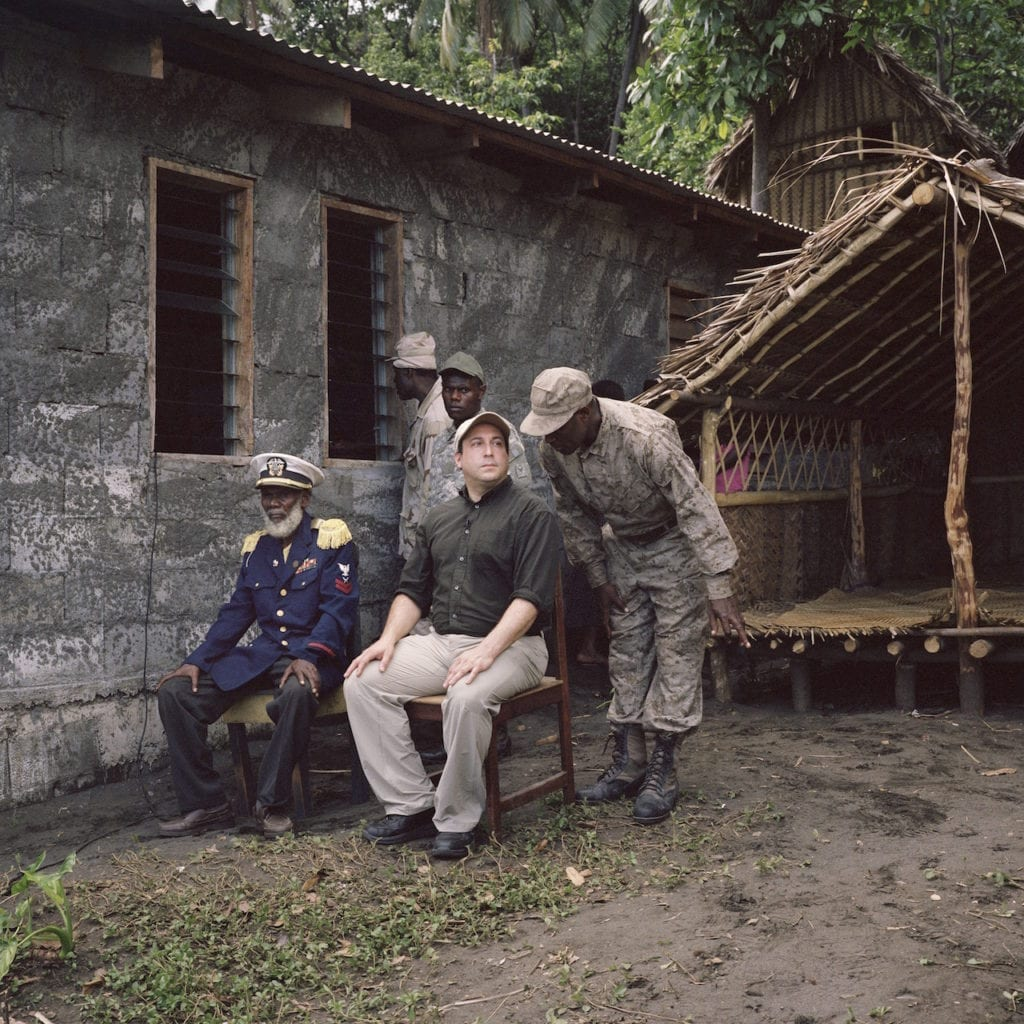 Chief Isaak of the John Frum Movement, at their village in Sulphur Bay on Tanna, sits overlooking the celebrations with Cevin during John Frum Day, February 2014. From the series Cargo © Jon Tonks