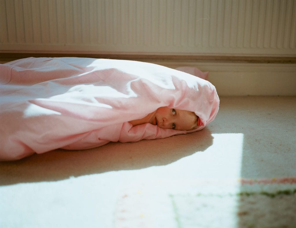 Plum cocooned by a pink duvet. From the series My Favourite Colour Was Yellow © Kirsty MacKay