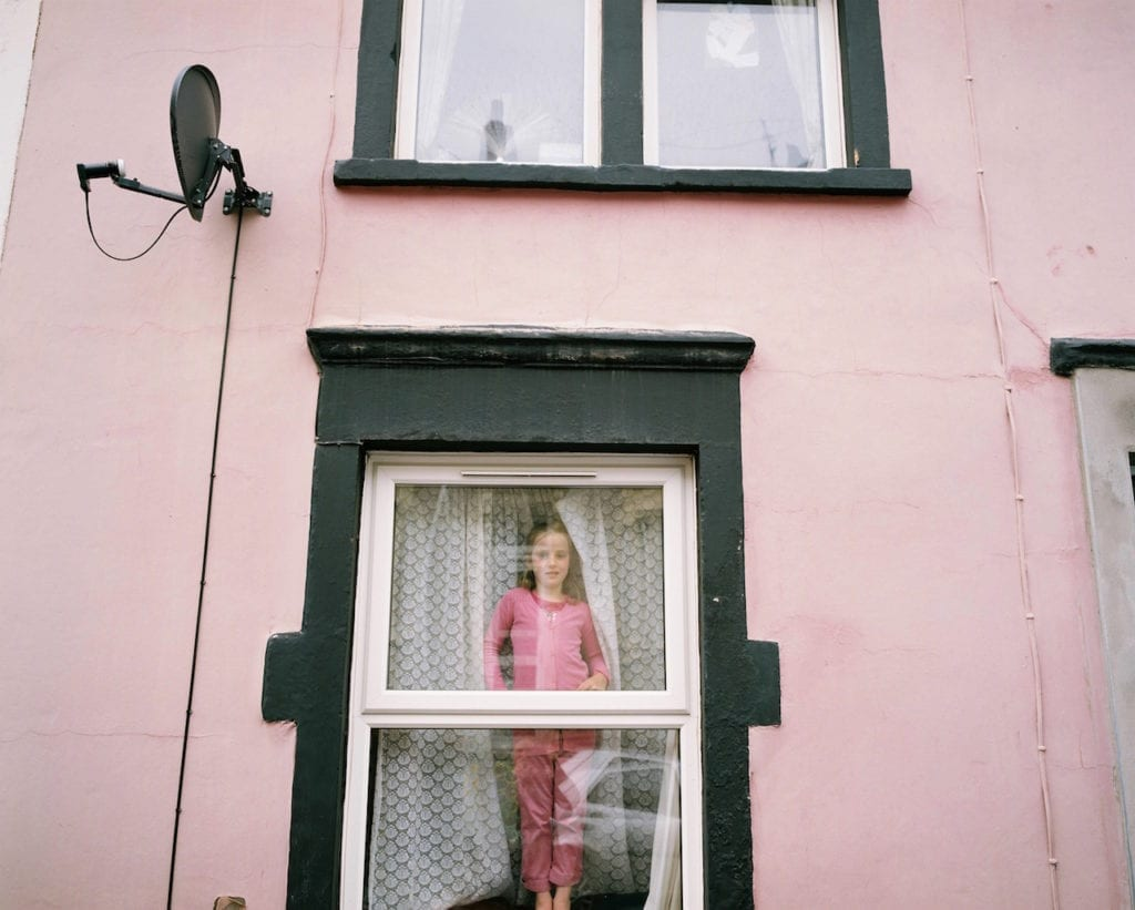 Liilly looking out from her pink house, Totterdown, Bristol. From the series My Favourite Colour Was Yellow © Kirsty MacKay