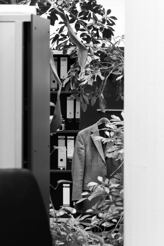 Overgrown suit jacket and filing cabinet, open space office, private bank, Stuttgart. From the series Büropflanze