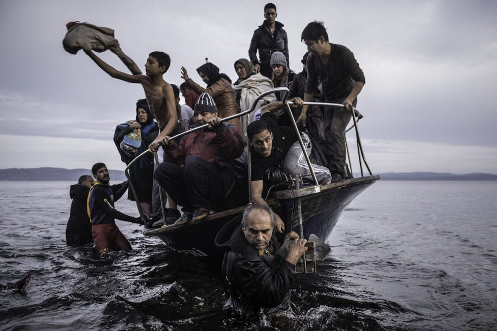 Migrants arrive by a Turkish boat near the village of Skala, on the Greek island of Lesbos. The Turkish boat owner delivered some 150 people to the Greek coast and tried to escape back to Turkey; he was arrested in Turkish waters. November 16, 2015, from the series Europe Migration Crisis © Sergey Ponomarev, courtesy Prix Pictet