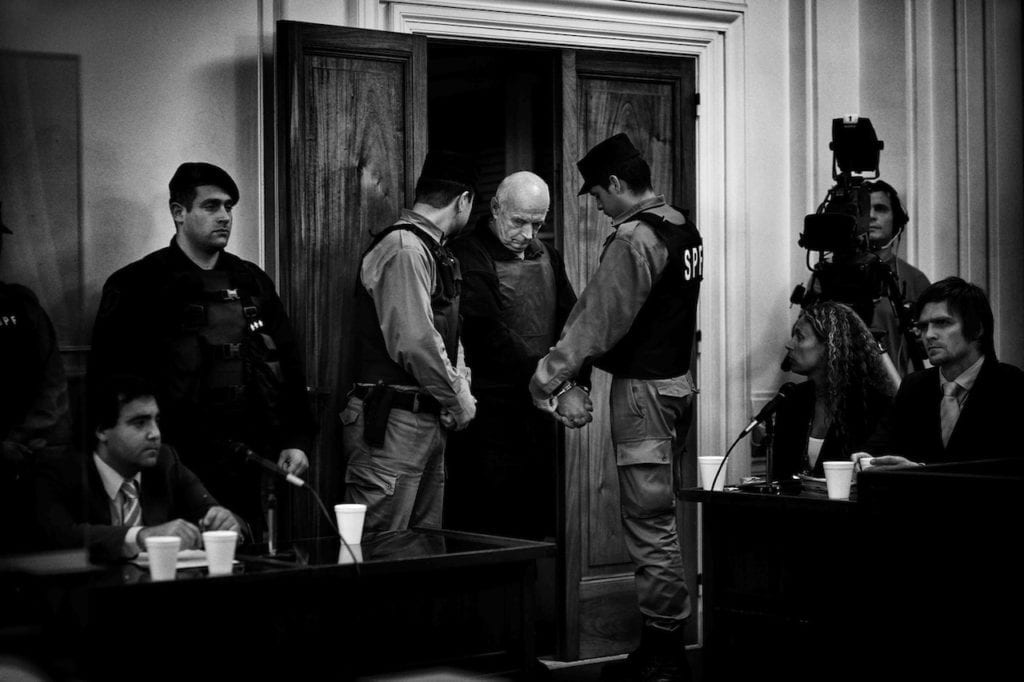 Von Wernich, wearing a bullet-proof vest, enters the courtroom before the verdict. The court found him guilty of complicity in seven homicides, 42 kidnappings, and 32 instances of torture and sentenced him to life imprisonment. La Plata, Buenos Aires Province, Argentina, 2007 © Giancarlo Ceraudo, courtesy of the artist