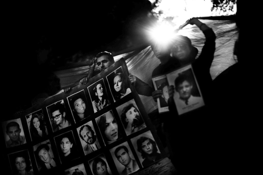 People holding some photographs of desaparecidos at a public rally during the anniversary of the 1976 military coup. Buenos Aires, Argentina, 24 March 2011 © Giancarlo Ceraudo, courtesy of the artist