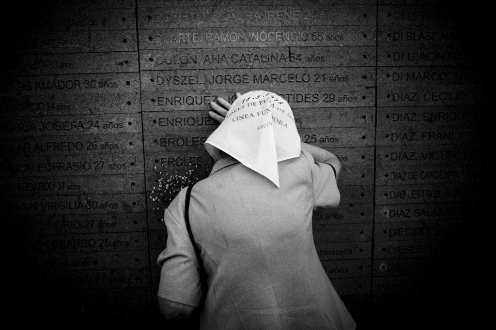One of the Mothers of Plaza de Mayo cries on her son's name inscribed on the wall of the Park of Memory, the Monument to the Victims of State Terrorism located along the coastline of the Río de la Plata river. Buenos Aires, Argentina, 2007 © Giancarlo Ceraudo, courtesy of the artist